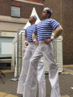 Muscled stilt walking sailors